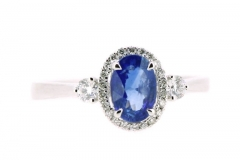 18ct white gold oval cut sapphire ring featuring diamond shoulders and halo