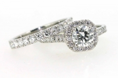 Handmade platinum round brilliant engagement ring featuring diamond halo and band